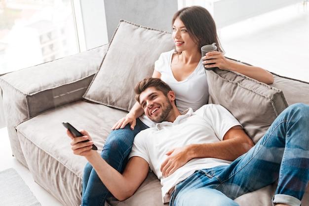 Jovem casal sorridente relaxando e assistindo tv em casa Foto Premium