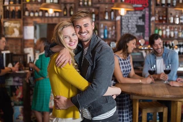 Jovem casal sorridente se abraçando em um bar