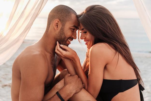 Jovem casal sorridente se abraçando na cama na praia