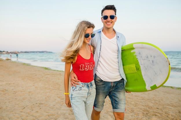Jovem casal sorridente se divertindo na praia caminhando com prancha de surf