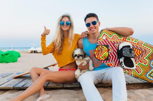 Jovem casal sorridente se divertindo na praia com uma prancha de kitesurf nas férias de verão
