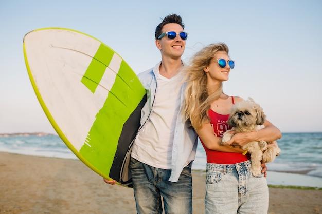 Jovem casal sorridente se divertindo na praia, posando com uma prancha de surf, brincando com um cachorro