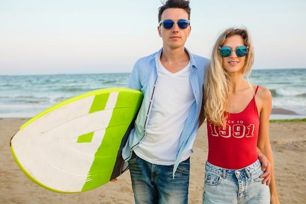 Jovem casal sorridente se divertindo na praia, posando com uma prancha de surf