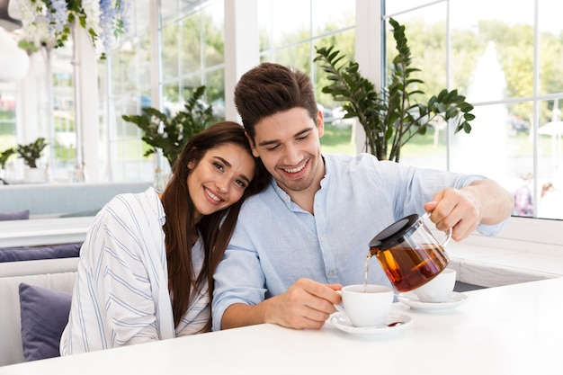 Jovem casal sorridente, sentado à mesa do café, bebendo chá