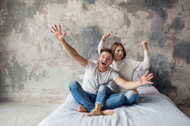 Jovem casal sorridente, sentado na cama em casa com roupa casual, homem e mulher se divertindo juntos, emoção positiva louca, feliz, segurando as mãos para cima