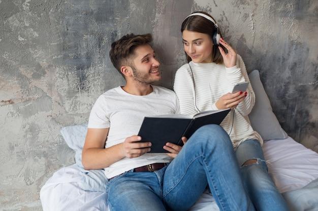 Jovem casal sorridente, sentado na cama em casa com roupa casual, lendo um livro de jeans, um homem lendo um livro, uma mulher ouvindo música em fones de ouvido e passando um tempo romântico juntos