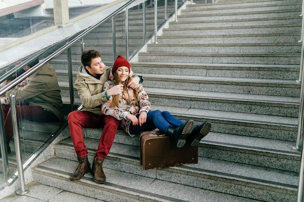 Jovem casal sorridente, sentado na escada.