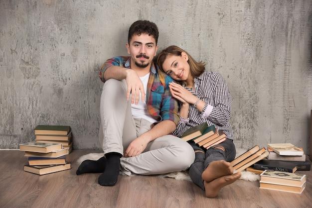 Jovem casal sorridente sentado no chão com livros