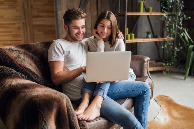 Jovem casal sorridente, sentado no sofá em casa com roupa casual, amor e romance, mulher e homem se abraçando, vestindo jeans, relaxando juntos, segurando um laptop