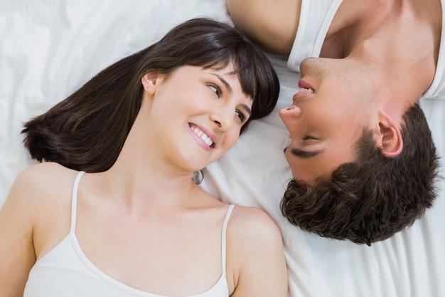 Jovem casal sorrindo e deitada na cama no quarto