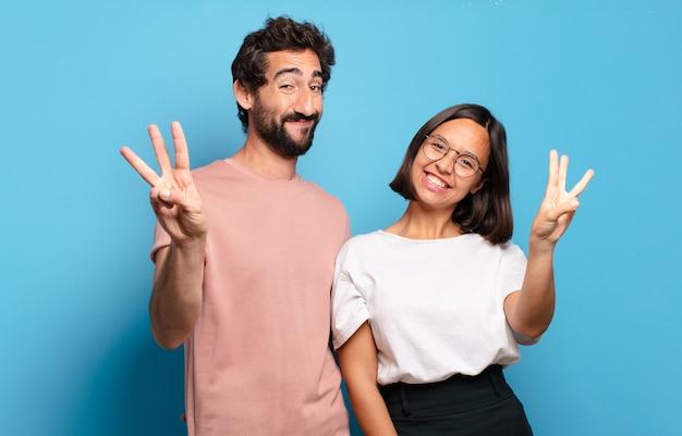 Jovem casal sorrindo e parecendo amigável, mostrando o número três ou o terceiro com a mão para a frente, em contagem regressiva