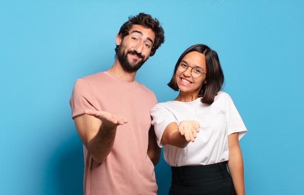 Jovem casal sorrindo feliz com um olhar amigável, confiante e positivo, oferecendo e mostrando um objeto ou conceito