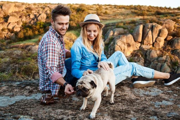 Jovem casal sorrindo, sentado na pedra no canyon, acariciando o cão pug