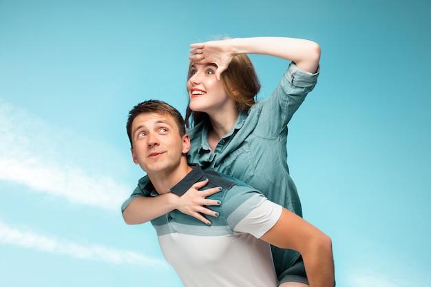 Jovem casal sorrindo sob o céu azul