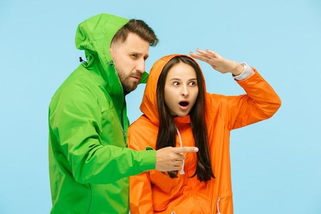 Jovem casal surpreso, apontando para a esquerda e posando no estúdio em jaquetas de outono isoladas em azul. emoções negativas humanas. conceito de clima frio. conceitos de moda feminina e masculina