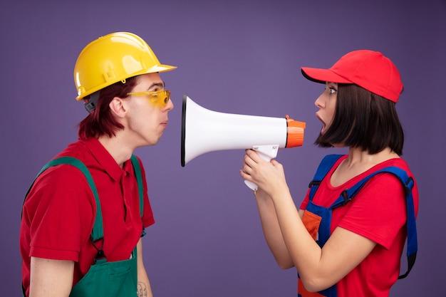 Jovem casal surpreso com uniforme de trabalhador da construção civil em pé em vista de perfil, olhando um para o outro cara usando capacete de segurança e óculos de segurança garota usando boné segurando alto-falante