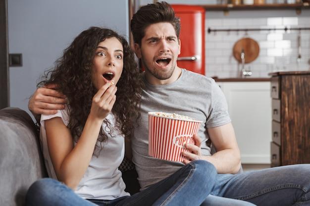 Jovem casal surpreso, homem e mulher, sentados no sofá em casa comendo pipoca no balde