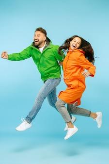 Jovem casal surpreso no estúdio em jaquetas de outono isoladas em azul. emoções positivas felizes humanas. conceito de clima frio. conceitos de moda feminina e masculina