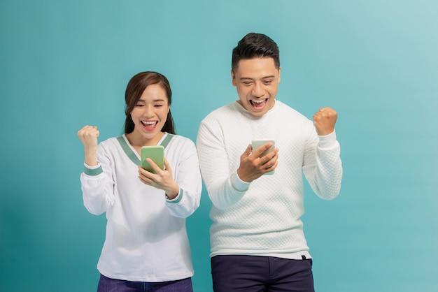 Jovem casal surpreso parado isolado no azul segurar smartphones feliz ganhar na loteria online