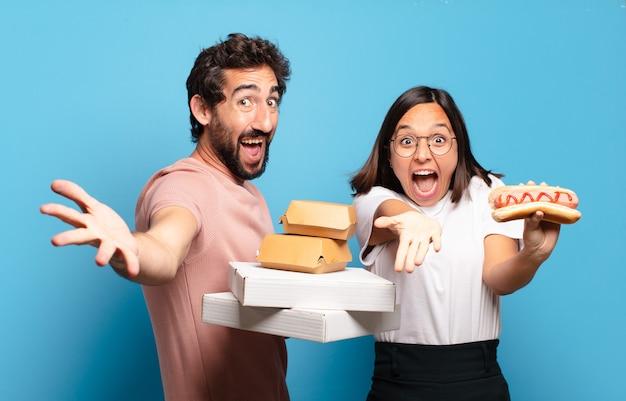 Jovem casal tendo levar fast food para casa.