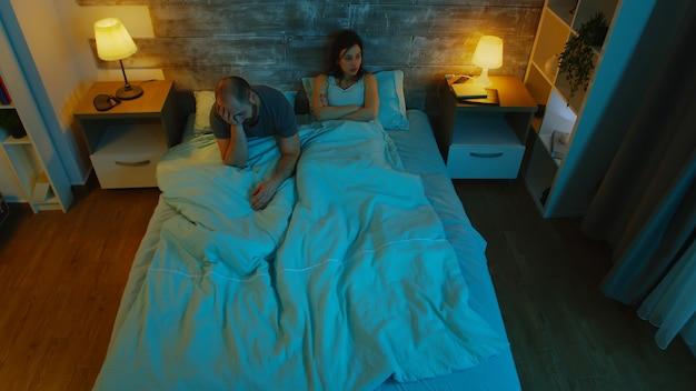 Jovem casal tendo uma conversa de argumento à noite, debaixo dos lençóis. luz da lua azul. casal infeliz.