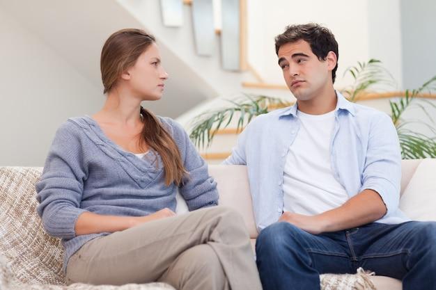 Jovem casal tendo uma discussão enquanto assiste tv