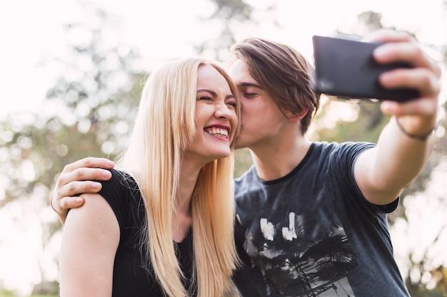 Jovem casal tira uma selfie. casal feliz no parque.
