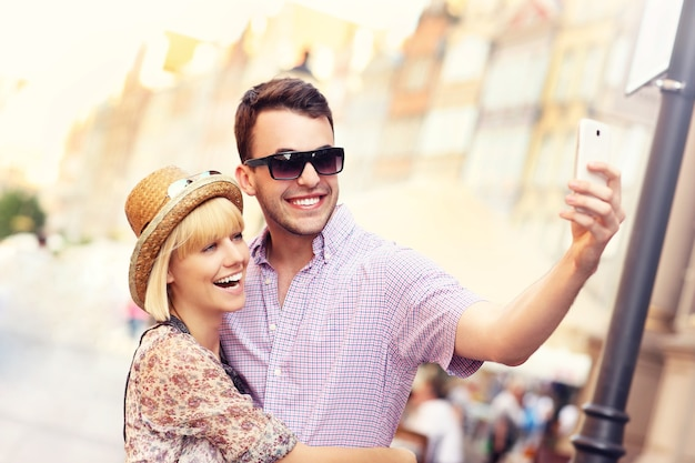 Jovem casal tirando uma selfie enquanto viaja por gdansk, na polônia