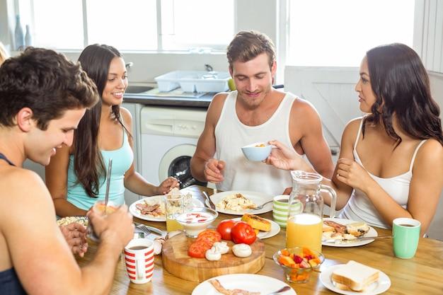 Jovem casal tomando café da manhã com os amigos em casa