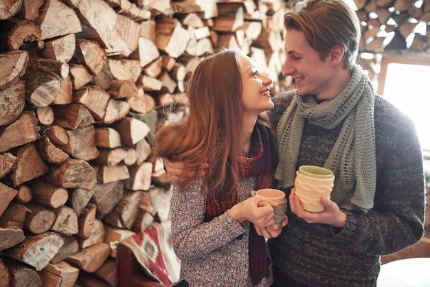 Jovem casal tomando café da manhã em uma cabine romântica ao ar livre no inverno. férias de inverno e férias. casal de natal de homem e mulher feliz bebem vinho quente. casal apaixonado