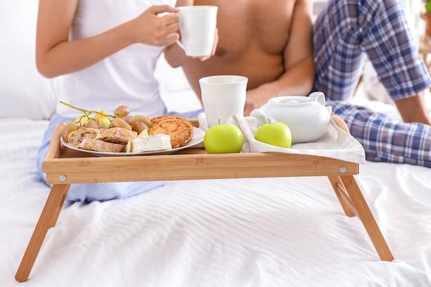 Jovem casal tomando café da manhã na cama