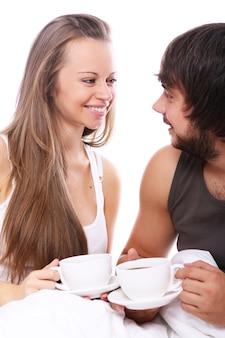 Jovem casal tomando café na cama