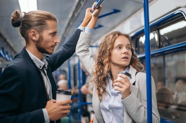 Jovem casal tomando café para viagem em um vagão do metrô