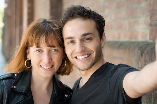 Jovem casal tomando selfie com telefone móvel ao ar livre.