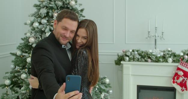 Jovem casal tomando selfie no celular em fundo de decoração de natal. homem segura um celular na mão e tira uma selfie com sua esposa.