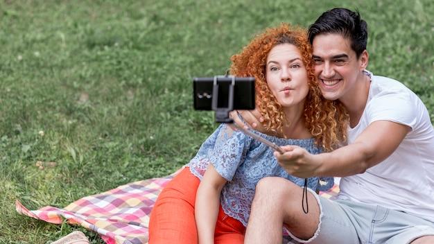 Jovem casal tomando selfies e se divertindo durante um piquenique