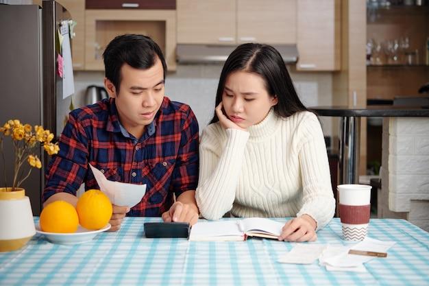 Jovem casal triste e carrancudo, sentado à mesa da cozinha e olhando para a calculadora com a soma das despesas mensais