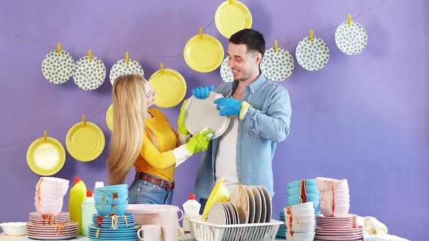 Jovem casal, um homem e uma mulher, olhando um para o outro, lava e limpa pratos e pratos. felicidade, família faz tudo junto