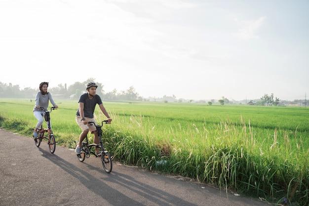Jovem casal usa capacete para andar de bicicleta dobrável nos campos de arroz