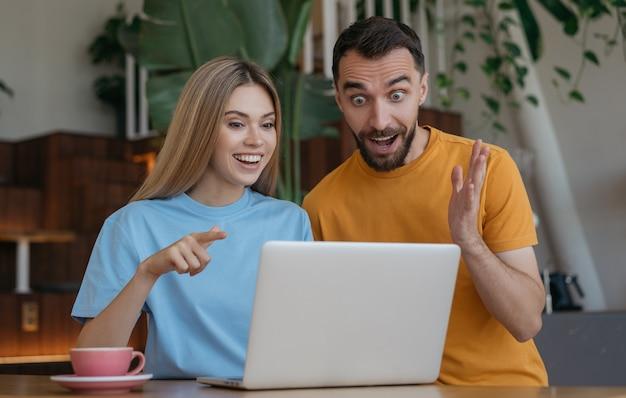Jovem casal usando laptop, compras online em casa. homem emocional e mulher assistindo filme juntos