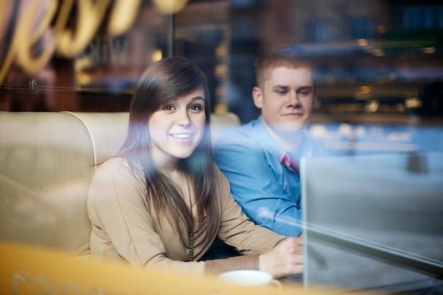 Jovem casal usando laptop em uma cafeteria