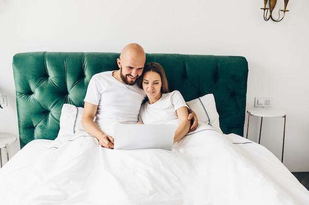 Jovem casal usando laptop juntos na cama.