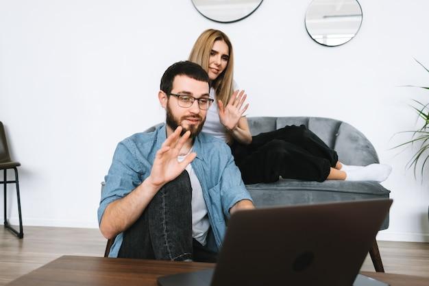 Jovem casal usando laptop, olhando para a tela do laptop na videochamada e saudando com acenando na moderna sala de estar.