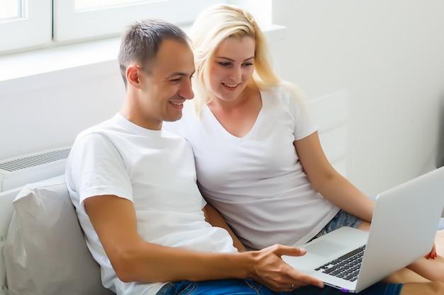 Jovem casal usando o laptop na mesa em casa e pensar