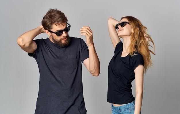 Jovem casal usando óculos escuros camisetas pretas roupas casuais estilo de vida estúdio