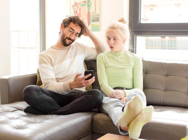 Jovem casal usando smartphone em casa