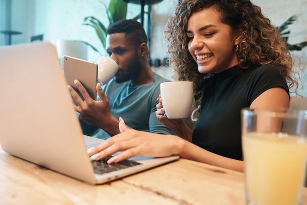 Jovem casal usando um laptop e tablet digital enquanto está sentado em uma mesa em casa.