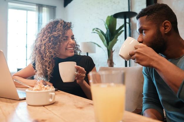 Jovem casal usando um laptop enquanto tomam café da manhã juntos em casa.