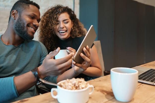 Jovem casal usando um tablet digital enquanto tomam café da manhã juntos em casa.