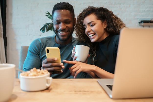 Jovem casal usando um telefone celular enquanto tomam café da manhã juntos em casa.